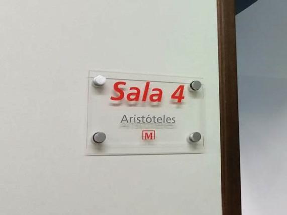 Letrero para señalización de espacio en oficinas interiores o exteriores: placa de cristal rotulada con vinil en colores corporativos y separadores tipo chapetones para montaje en pared.