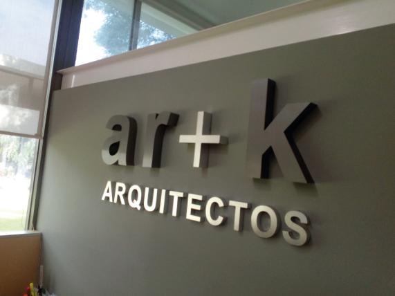 Logotipo 3D en aluminio recortado, acabado natural y esmaltado en colores corporativos, montado en pared de recepción al interior de las oficinas.