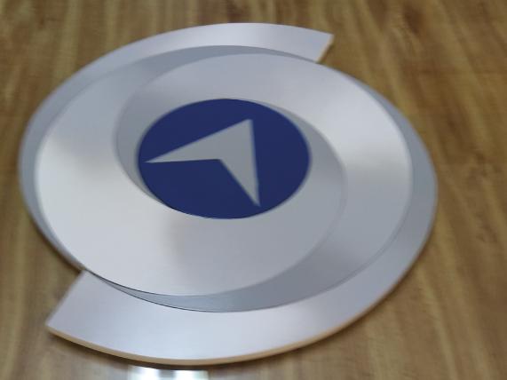 Logotipo en acero inoxicable acabados natural, cepillado y esmaltado, con respaldo de trovicel blanco para montaje en interiores de oficina.