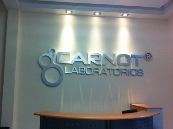 Logotipo 3D en aluminio cepillado acabado mate para recepción en interior de oficinas.