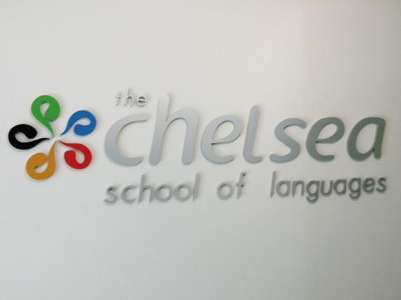 Logotipo recortado en aluminio natural, acabado cepillado y esmaltado en colores corporativos, con respaldo de acrílico y montado sobre pared en interior de colegio.